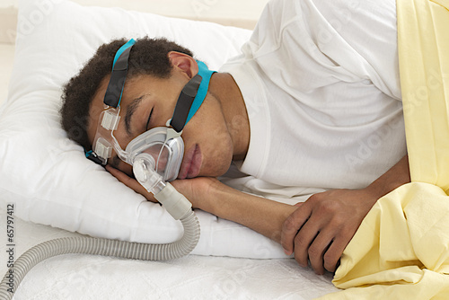 young mulatto man  sleeping with apnea and CPAP machine - 65797412