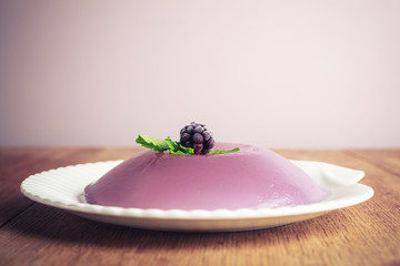 Closeup on a purple pudding with a blackberry