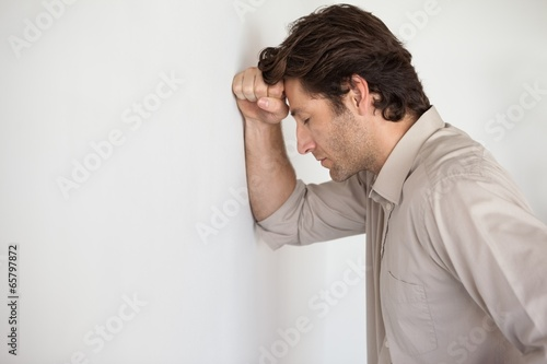 Poster Wand Casual worried businessman leaning head on wall
