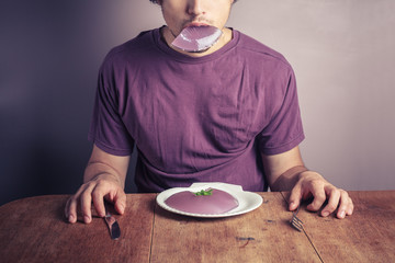 Young man eating purple pudding