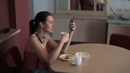 Woman texting on smartphone by the table at home