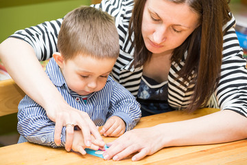 Mother and child boy drawing together with color pencils