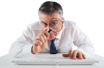 Mature businessman examining with magnifying glass