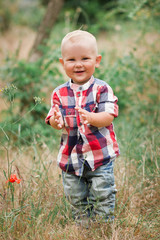 Fashion baby boy wearing checkered shirt walking in grass