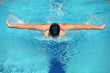 swimmer in cap performing the butterfly stroke