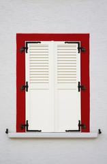 Geschlossener Klappladen und rote Fenstereinfassung