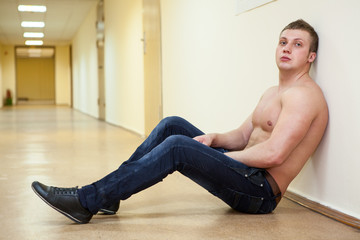 Depressive man shirtless sitting in long corridor