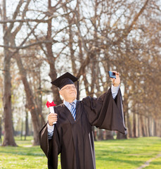 Mature man holding diploma and taking selfie in park