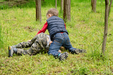 Two young boys fighting on the ground