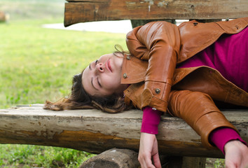 Exhausted woman sleeping on a wooden bench