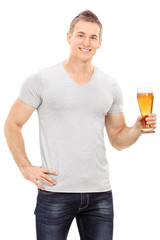 Handsome young man holding a pint of beer