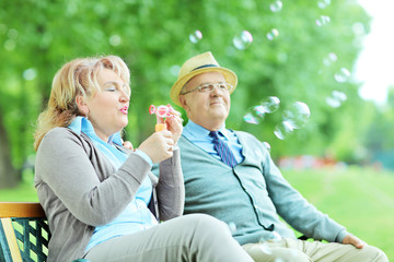 Carefree mature couple blowing bubbles in park