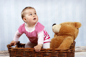 Little baby in the wicker basket with teddy bear