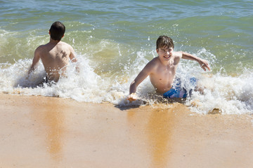 boys are playing  in a beautiful sea with crystal clear water