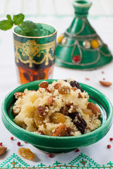 Moroccan couscous with dried fruit and nuts in tajíne