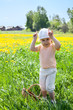 Small Caucasian girl playing on meadow in cow