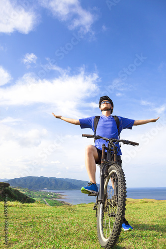 young backpacker sitting on a  mountain bike and relaxing pose