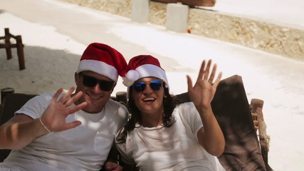 Couple smiling to the camera and wearing santas hats, steadycam