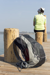 Woman sitting on the boat dock and resting from the hike from