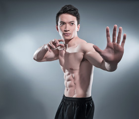 Muscled asian kung fu man in action pose. Blood stripes on his c