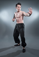 Muscled asian kung fu man in action pose with nunchucks. Blood s
