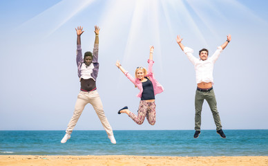 Multiracial friends jumping at the beach
