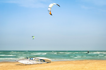 Kite surfing at tropical beach with windsurf board