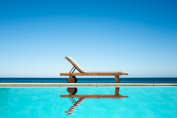 Reclining chair near a swimming pool, sea background