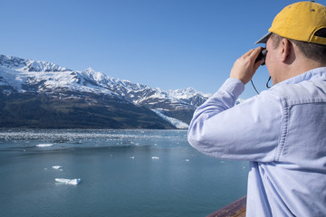 Man Looking at Mountains with a Binoculars