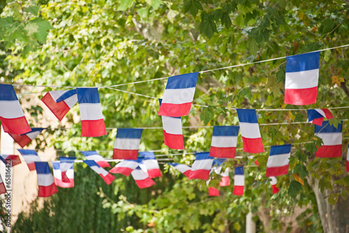 French flags garland decorating a village square, Bastille day, July 14th national day concept - 65816423