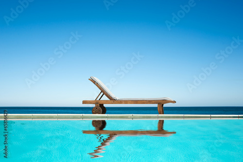 Reclining chair near a swimming pool, sea background - 65816429