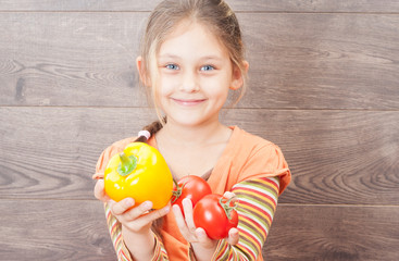 beautiful girl holding a tomato on a wooden background