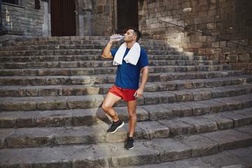 Male runner drinks water after a tiring morning jog