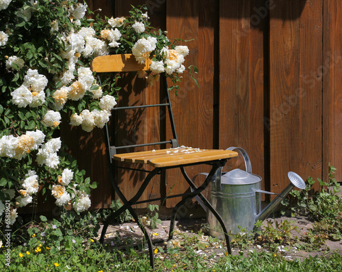 Garden chair with roses and watering can © Marina Lohrbach