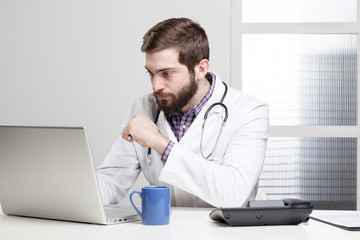 Doctor using phone and computer while at work