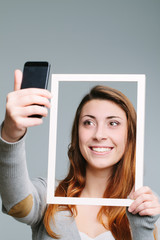 woman taking a selfie and holding picture frame