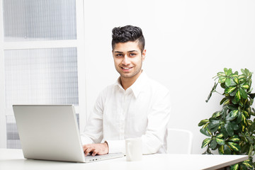 Young Asian Indian Businessman working on laptop