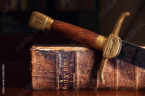 Leinwanddruck Bild Old Bible With Sword