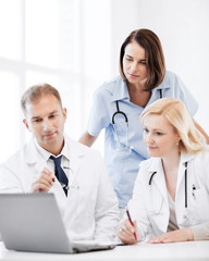 doctors looking at laptop on meeting