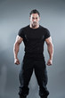 canvas print picture - Combat muscled fitness man wearing black shirt and pants. Studio