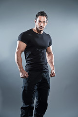 Combat muscled fitness man wearing black shirt and pants. Studio