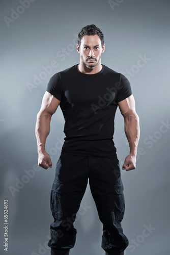 canvas print picture Combat muscled fitness man wearing black shirt and pants. Studio