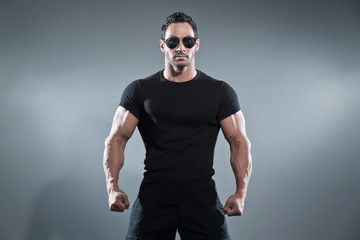 Combat muscled action hero man wearing black t-shirt with pants