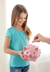 smiling little girl holding piggy bank