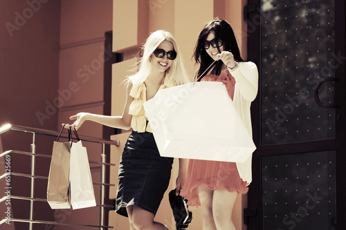 Two happy young women with shopping bags