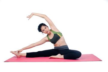 Beautiful woman indoor exercising using pink yoga mat
