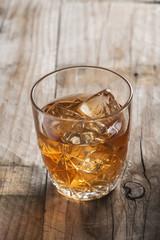 Vaso de licor con hielos whiskey cognac ron en la mesa del bar