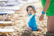 Small boy playing with sand at the beach with mom beside