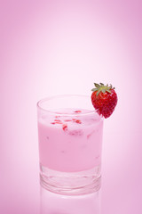Fresh strawberry smoothie on pink background