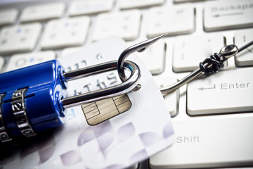 fish hook with a credit card and security lock on keyboard